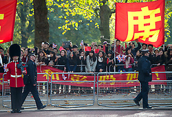 © Licensed to London News Pictures. 20/10/2015. London UK. Chinese people line the sides of The Mall in London as a carriage carrying Queen Elizabeth II and President Xi Jinping makes its way along the Mall to Buckingham Palace as Chinese President Xi Jinping starts day one of a four day State Visit to the United Kingdom. Photo credit: Ben Cawthra/LNP