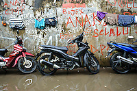 Motorbikes parked in a flooded street, Tallo, Makassar, Sulawesi, Indonesia.