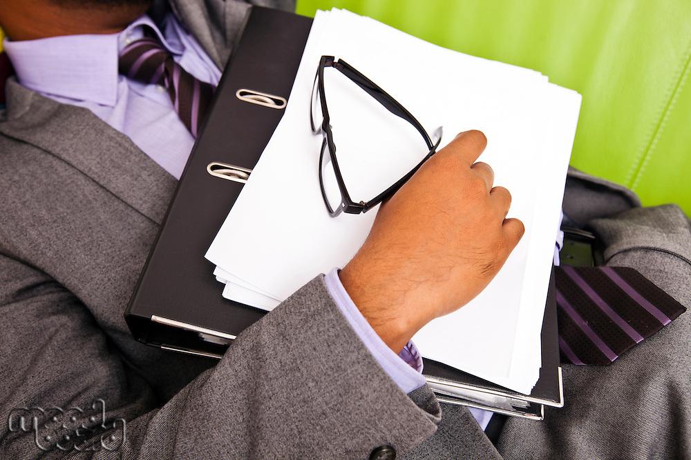 Close up of sleeping businessmans hand holding folder