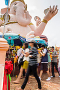 "29 SEPTEMBER 2012 - NAKORN NAYOK, THAILAND:  Thai Buddhists process around a statue of Ganesh during observances of Ganesh Ustav at Wat Utthayan Ganesh, a temple dedicated to Ganesh in Nakorn Nayok, about three hours from Bangkok. Many Thai Buddhists incorporate Hindu elements, including worship of Ganesh into their spiritual life. Ganesha Chaturthi also known as Vinayaka Chaturthi, is the Hindu festival celebrated on the day of the re-birth of Lord Ganesha, the son of Shiva and Parvati. The festival, also known as Ganeshotsav (""festival of Ganesha"") is observed in the Hindu calendar month of Bhaadrapada, starting on the the fourth day of the waxing moon. The festival lasts for 10 days, ending on the fourteenth day of the waxing moon. Outside India, it is celebrated widely in Nepal and by Hindus in the United States, Canada, Mauritius, Singapore, Thailand, Cambodia, Burma , Fiji and Trinidad & Tobago.     PHOTO BY JACK KURTZ"