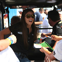 Danica Patrick leaves the main stage area of the FanZone to a throng of fans after her interview session prior to the NASCAR Coke Zero 400 Sprint series auto race at the Daytona International Speedway on Saturday, July 6, 2013 in Daytona Beach, Florida.  (AP Photo/Alex Menendez)