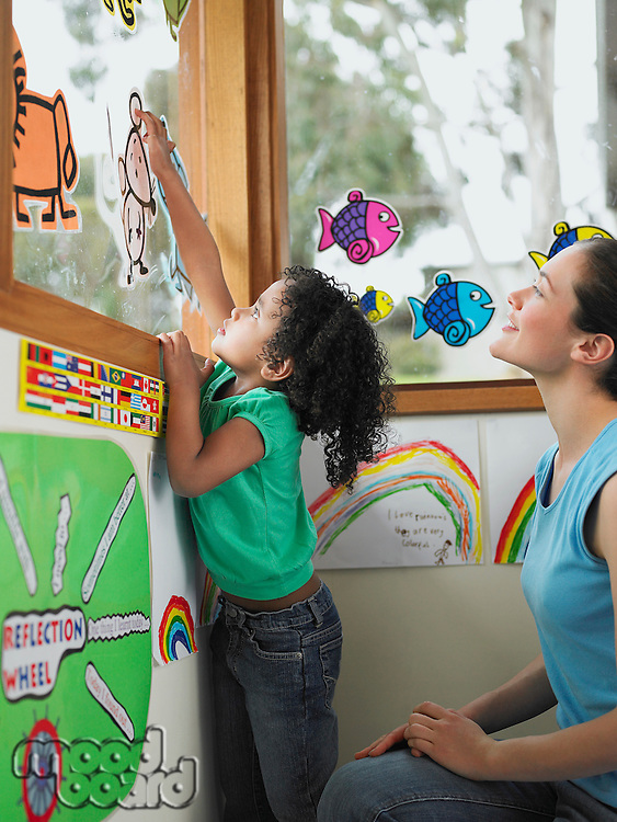 Girl decorating school window with cut out drawings