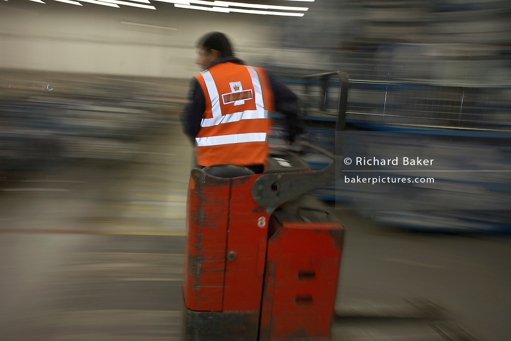 Speeding postal worker in the processing depot of Royal Mail's DIRFT logistics park in Daventry, Northamptonshire England.