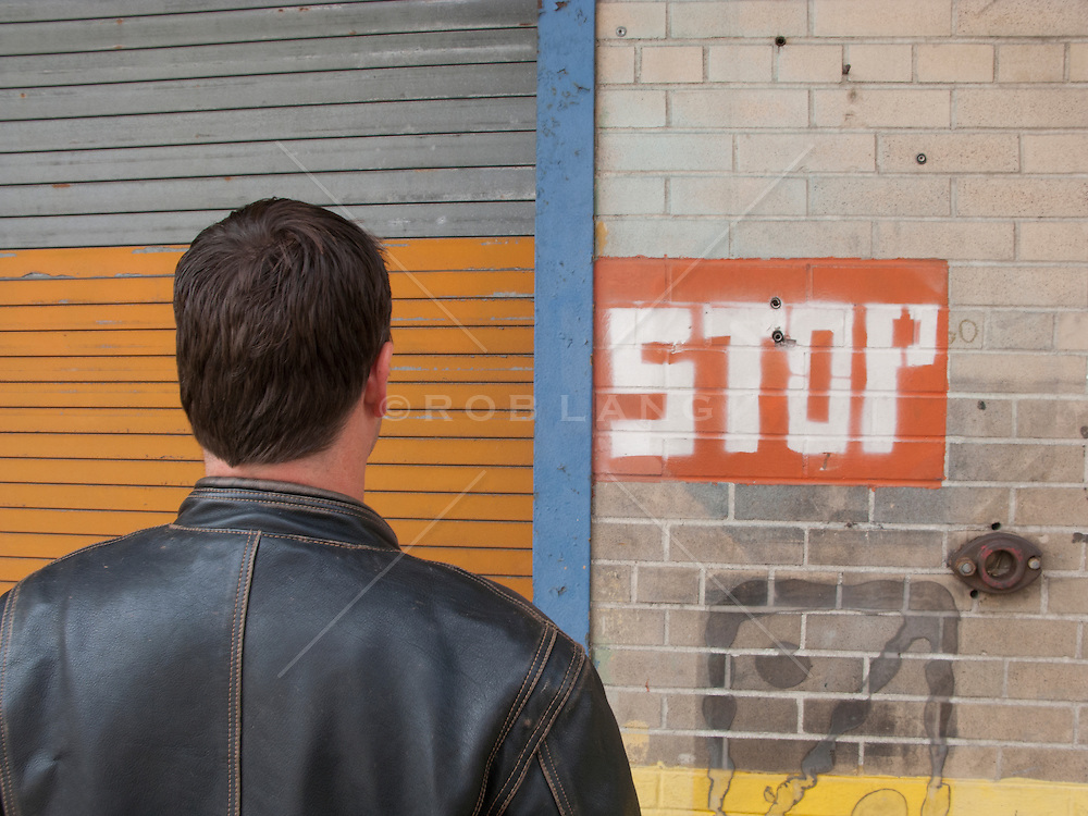 man standing in front of a hand painted stop sign on a wall