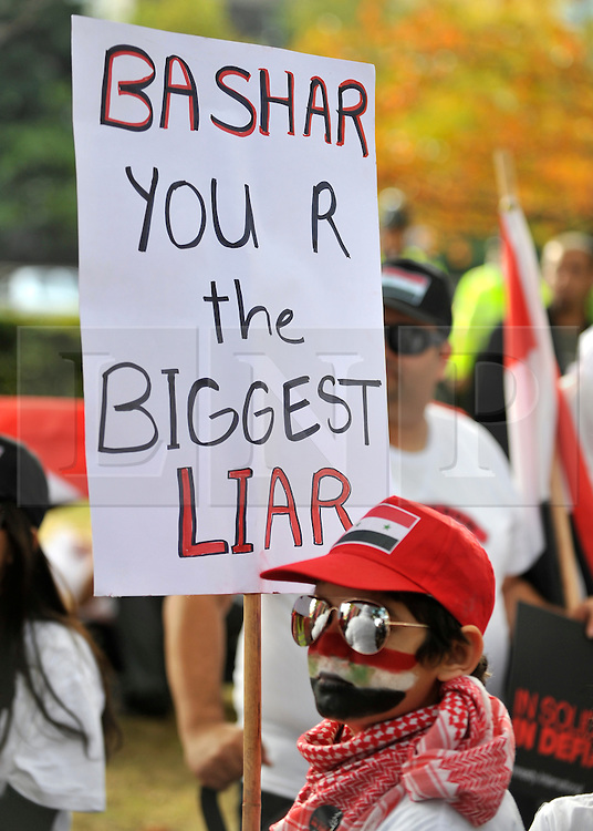 """35559258© Licensed to London News Pictures. 29/10/2011. London, UK.  A young boy carries a banner calling Syrian President Bashar Assad a liar. Amnesty International join Syrians in the UK for a """"N0 More Blood - No More Fear"""" march and rally in Paddington Green, London, today 29th October 2011. Activists claim  Syrian security forces opened fire on Friday on protesters and hunted them down in house-to-house raids, killing about 40 people in the deadliest day in weeks in the country's 7-month-old uprising. Photo: Stephen Simpson/LNP"""