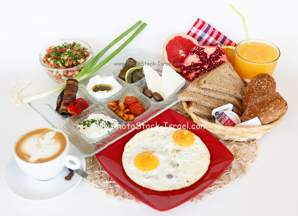 Traditional Israeli Breakfast with two fried eggs, cheeses, salad, a fresh roll orange juice and a cup of cappuccino