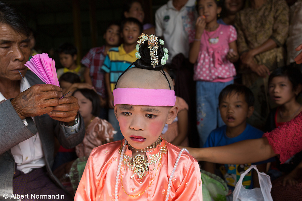 Young Novice Monk with upset, sad face as family and friends dress him for ceremonies, Sha Wa Gyi floating village