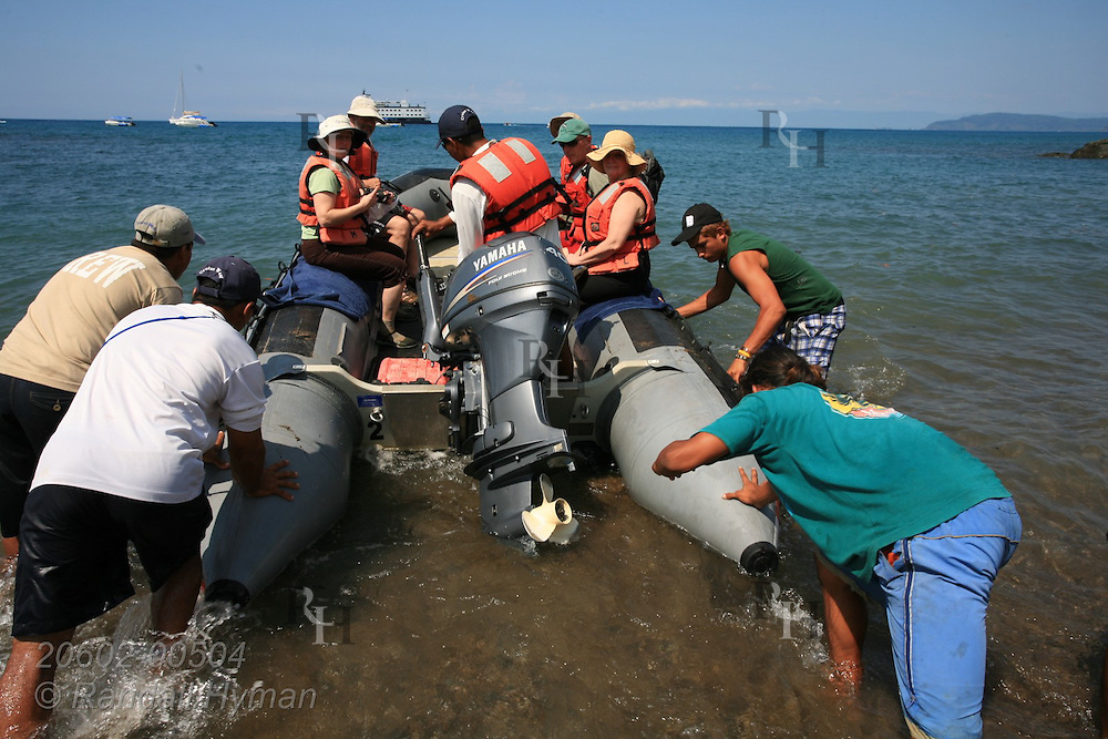 Cruise ship crew pushes boat full of passengers off Caletas Beach back to mother ship in Drake Bay on Pacific Ocean at Osa Peninsula near Corcovado National Park, Costa Rica.