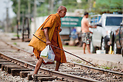 Mar 22, 2009 -- A Buddhist monk crosses the rail tracks in Samut Sakhon, Thailand. The Mahachai Rail Line is a commuter line that runs from the Wong Wian Yai train station in the Thonburi section of Bangkok to the fishing port and market town of Samut Sakhon, which used to be known as Mahachai. A second line from Baan Laem to Samut Songkhram, another fishing port south of Samut Sakhon. Each stretch of the line takes about an hour.    Photo by Jack Kurtz