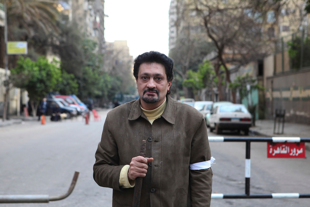 A man from neighborhood watch stands guard in downtown Cairo. .