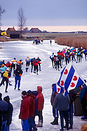 Nederland, Molkwerum, 19970104..De Elfstedentocht in januari 1997 in Friesland..Schaatsers rijden door de polders. Koek en zoopie tent met de Friese vlag. Mensen staan te kijken naar de schaatsers die voorbij komen terwijl de avond valt. Eenzame boerderijen..Schemering. 6000 schaatsers en meer dan een miljoen toeschouwers...The Elfstedentocht is a speed skating competition and leisure skating tour in the province of Friesland in the Netherlands..Skaters driving towards the setting sun.6.000 skaters and over a million spectators were present. The route takes the skaters through eleven cities in Frisia, in the North of Holland. Flag of the provence Friesland. 200 kilometre race along the frozen canals of Friesland..Skaters ride through the polders. Cake and zoopie tent with the Frisian flag. People are watching the skaters that come as evening falls. Isolated farms.