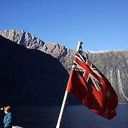 Tourists on a cruise ship on Milford Sound, South Island, New Zealand..Milford Sound (Piopiotahi in Ma¯ori) is a fjord in the south west of New Zealand's South Island, within Fiordland National Park and the Te Wahipounamu World Heritage site. It has been judged the world's top travel destination and is acclaimed as New Zealand's most famous tourist destination..Milford Sound runs 15 kilometres inland from the Tasman Sea at Dale Point - the mouth of the fiord - and is surrounded by sheer rock faces that rise 1,200 metres (3,900 ft) or more on either side. Among the peaks are The Elephant at 1,517 metres (4,977 ft), said to resemble an elephant's head and The Lion, 1,302 metres (4,272 ft), in the shape of a crouching lion. Lush rain forests cling precariously to these cliffs, while seals, penguins, and dolphins frequent the waters and whales can be seen sometimes..Milford Sound sports two permanent waterfalls all year round, Lady Bowen Falls and Stirling Falls. After heavy rain many hundreds of temporary waterfalls can be seen running down the steep sided rock faces. .The beauty of this landscape draws thousands of visitors each day, with between 550,000 and 1 million visitors in total per year. This makes the sound one of New Zealand's most-visited tourist spots, and also the most famous New Zealand tourist destination.  Milford Sound, New Zealand. 29th April 2011. Photo Tim Clayton