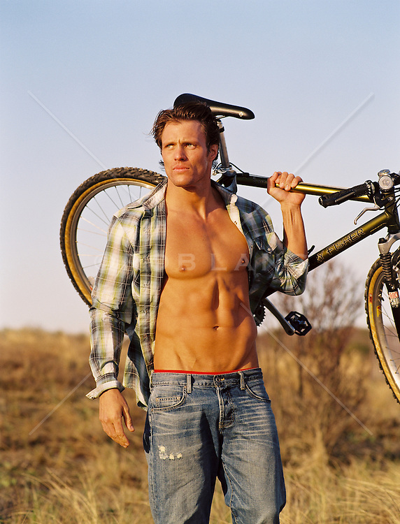 Muscular young man with his shirt open carrying his mountain bike on his shoulder