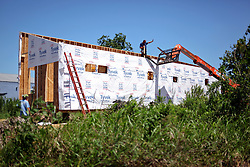 26 August 2015. New Orleans, Louisiana. <br /> Hurricane Katrina revisited. <br /> Rebuilding the Lower 9th Ward. <br /> A new 'Make it Right' house takes shape on Tennessee Street. Eco friendly 'Make it Right' homes inspired by actor Brad Pitt continue to provide hope for the rebirth of the community following the devastation of hurricane Katrina a decade earlier.<br /> Photo credit©; Charlie Varley/varleypix.com.