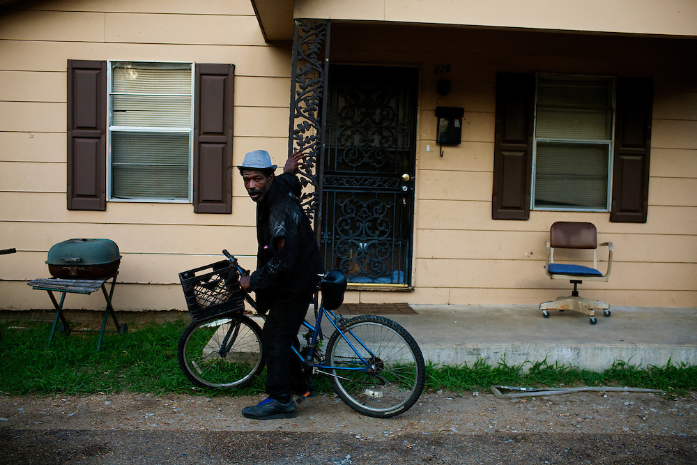 Frank Stringfellow drunkenly stands with his bike in the Baptist Town neighborhood of Greenwood, Mississippi on Friday, July 2, 2010.