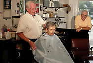 "Ralph Williams (left) cuts the hair of long-time customer David Moyer, from Springboro as Don Stoneking looks on at Scotty's Barber Shop, Wednesday, June 27th.  Moyer says that Williams cut his hair at ""The Annex"" in Middletown in the 1950's.  Stoneking says that he's been coming to Ralph for haircuts for the about three years, ""since I moved back from Florida."""