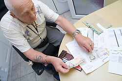 Male wheelchair user sitting at his kitchen table paying some bills,