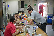 The crew on a Venezuelan oil drilling platform at lunch. Oswaldo Gutierrez (not in the photo), is the Chief of the PDVSA Oil Platform GP 19 in Lake Maracaibo, Venezuela, and works on the platform for seven days then is off at home for seven days.  Featured in the book What I Eat: Around the World in 80 Diets. Model Released..