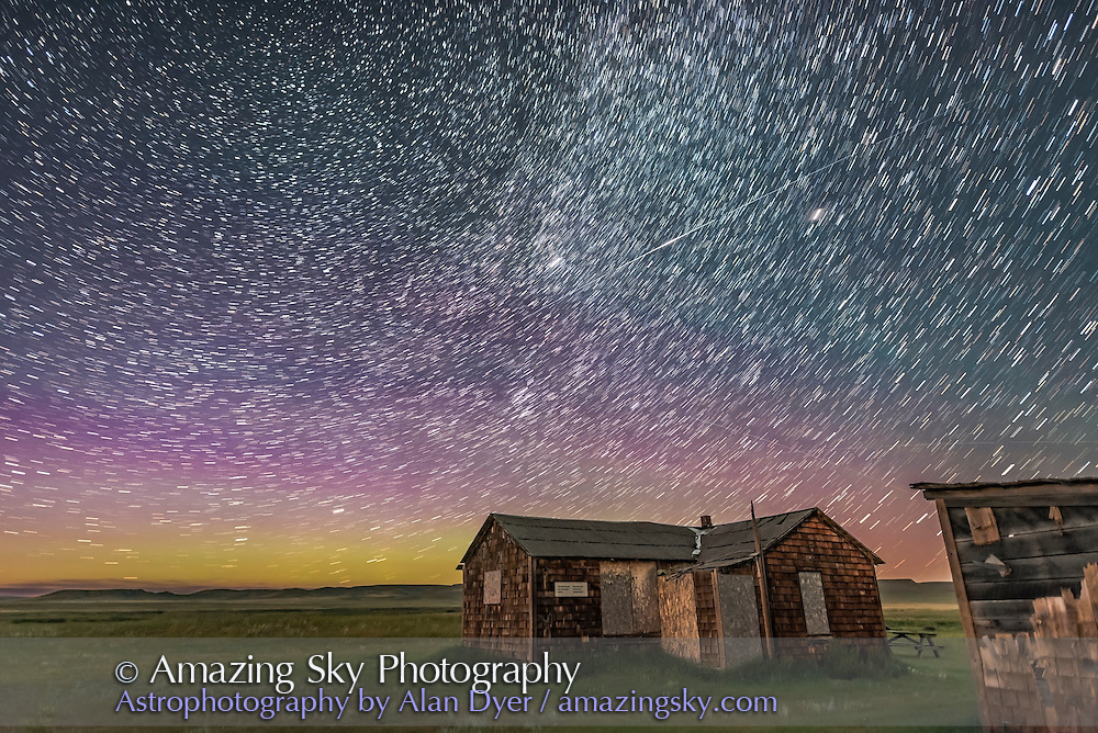 A flaring satellite, possibly and Iridium, over the oold pioneer Larson Ranch in the Frenchman River Valley in Grasslands National Park, Saskatchewan. <br /> <br /> This is a stack of 7 images taken at the start of a time-lapse sequence, each 30 seconds at f/2 with the Sigma 20mm lens and ISO 3200 with the Nikon D750.