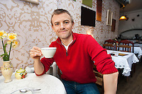 Portrait of happy young man holding coffee cup at cafe