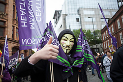 © Licensed to London News Pictures. 01/10/2017. Manchester, UK.  A protester wearing an Anonymous mask at the National Demonstration Against Austerity as part of the Take Back Manchester festival to protest the Conservative Party conference taking part in the city.  Photo credit: Steven Speed/LNP