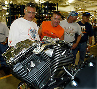 Four Harley riders from Vancouver Island, Canada admire a V-Twin engine for the just released 2004 Softail at the Harley-Davidson powertrain operations plant  in Milwaukee August 29, 2003. L-R are: Dean Bell, Dean Woods, Pat Jardine and Tim Berekoff.  Harley is celebrating its 100th anniversary and is expected to draw 200,000 to 300,000 people to the companies home base over four days.    REUTERS/Rick Wilking