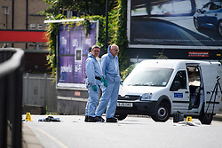 © Licensed to London News Pictures. 07/07/2016. London, UK. Police forensics officers stand over evidence markers and personal belongings at the scene where a man was struck by a car following an assault on Harrow Road in Harlesden, north west London. Photo credit: Ben Cawthra/LNP