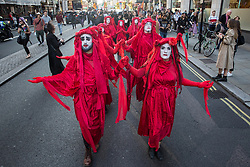 London, UK. 17 September, 2019. Red Brigade climate activists from Extinction Rebellion stage a RIP London Fashion Week Funeral March to call on both the public and the fashion industry to demand an end to London Fashion Week and the unsustainable system of consumption which it promotes. The event included a pause to reflect on the lives already lost and those that will be lost as a result of the climate and ecological crisis.