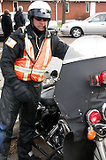 Motorcycle policeman ready to escort funeral procession to the cemetery.  East St Paul Minnesota USA