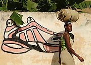 Southern Africa. Mozambique. Inhambane. .Woman carrying gas bottle on her head walking past grafitti of Addidas trainer..DVD0014
