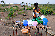 "A woman washes dishes outside her home in an area called 4 de Fevereiro on the outskrits of the Moxico provincial capital. The area was heavily contaminated with landmines during the country's long civil war and is the region's largest minefield. Returning refugees and displaced people as well as the government's ""Village Reunification Program,"" a program that encourages people living in remote hamlets to move into larger villages and towns so that the government can provide basic services such as education, health care, electricity and water to the population, has placed enormous pressure on the town to find safe land for people to live and to begin rebuilding their lives. Mines Advisory Group (MAG) is clearing the area of landmines and other remnents of the conflict to allow resettlement, housing and the long-term development of the country..Luena, Angola. 28/10/2010.Photo © J.B. Russell"