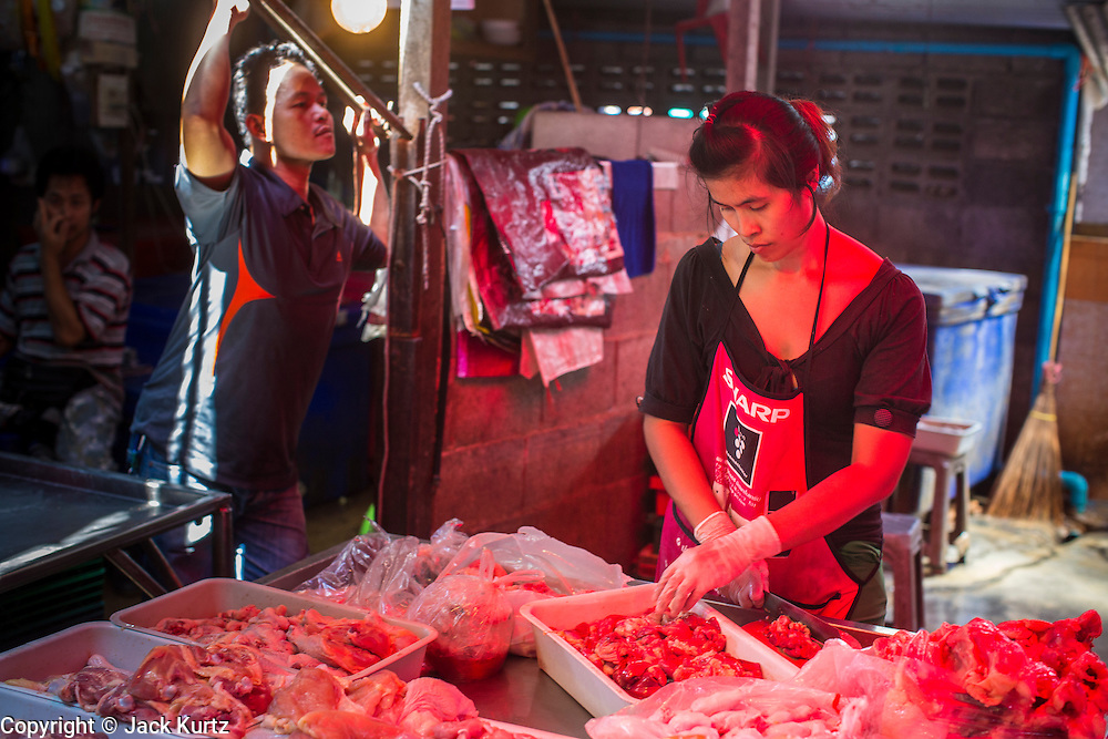 17 JANUARY 2013 - SAMUT SONGKHRAM, SAMUT SONGKHRAM, THAILAND: A meat vendor chops meat in the Samut Songkhram market. Four trains each day make the round trip from Baan Laem, near Samut Sakhon, to Samut Songkhram, the train chugs through market eight times a day (coming and going). Each time market vendors pick up their merchandise and clear the track for the train, only to set up again when the train passes. The market on the train tracks has become a tourist attraction in this part of Thailand and many tourists stop to see the train on their way to or from the floating market in Damnoen Saduak.    PHOTO BY JACK KURTZ