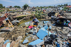 October 3, 2018 - Palu, Central Sulawesi, Indonesia - Agustin (51) washing clothes between the ruins of his house in Balaroa village after the earthquake in Palu..A deadly earthquake measuring 7.7 magnitude and the tsunami wave caused by it has destroyed the city of Palu and much of the area in Central Sulawesi. According to the officials, death toll from devastating quake and tsunami rises to 1,347, around 800 people in hospitals are seriously injured and some 62,000 people have been displaced in 24 camps around the region. (Credit Image: © Hariandi Hafid/SOPA Images via ZUMA Wire)