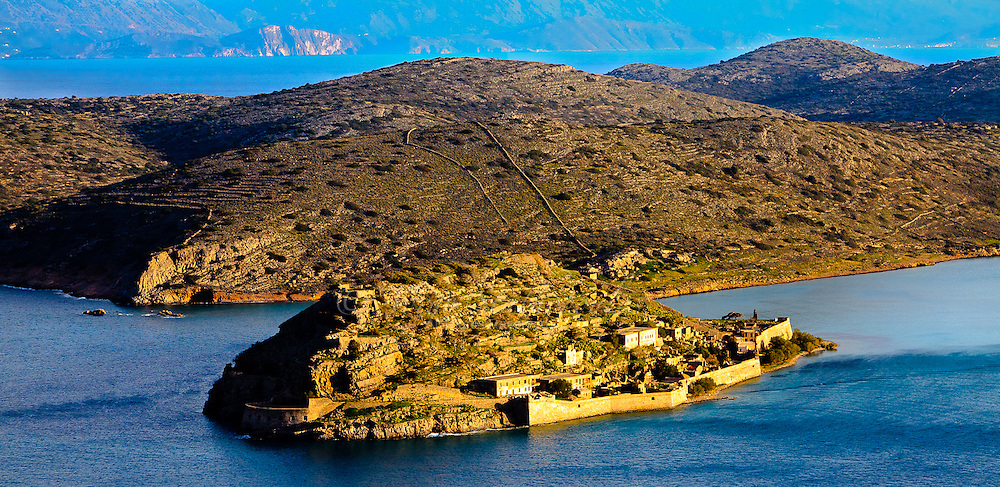 """The island of Spinalonga (official name: Kalidon) is located at the eastern section of Crete, in Lasithi prefecture, near the town of Elounda. The name of the island, Spinalonga, is Venetian, meaning """"long thorn"""", and has roots in the period of Venetian occupation."""