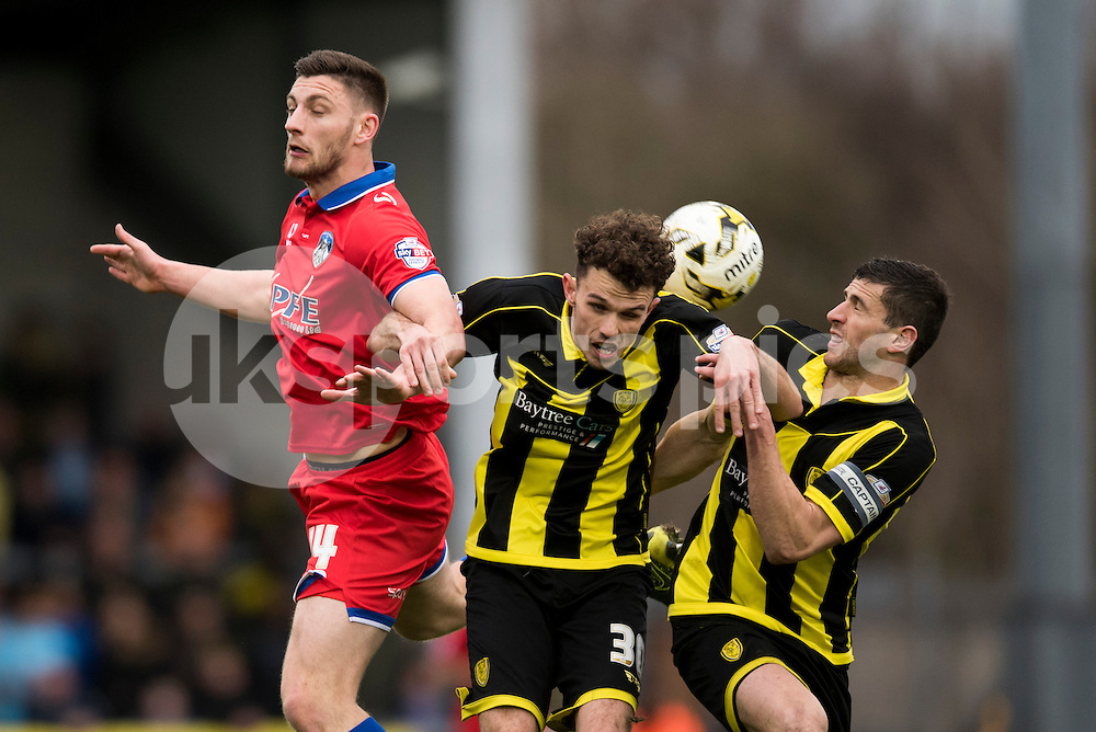 Tom Flanagan of Burton Albion, John Musinho of Burton Albion and Jake Cassidy of Oldham Athletic AFC compete for the ball during the Sky Bet League 1 match between Burton Albion and Oldham Athletic at the Pirelli Stadium, Burton upon Trent, England on 26 March 2016. Photo by Brandon Griffiths.