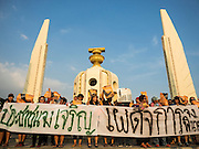 "19 SEPTEMBER 2015 - BANGKOK, THAILAND:  Anti coup protestors with a banner that says ""Long live the people, down with dictatorship"" gather at Democracy Monument in Bangkok. Hundreds of people protested against Thailand's military dominated government Saturday. The protest started with seminar about the 2006 coup that deposed popularly elected former Prime Minister Thaksin Shinawatra. After the seminar activists marched from Thammasat University to Democracy Monument, about 1 mile. Political gatherings of more than 5 people are banned by Thailand's military government and police tried to dissuade the protestors from finishing their march. Protestors ignored the police, who then stood by and watched but made no effort to intervene. At Democracy Monument protestors laid flowers and made speeches against the military. It was the largest anti-coup protest in Bangkok in more than a year.    PHOTO BY JACK KURTZ"