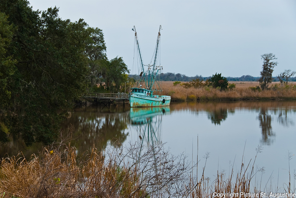 A lone shrimp boat rest at a dock in the marsh. This picture was taken on a cloudy morning in Darien, Georgia.