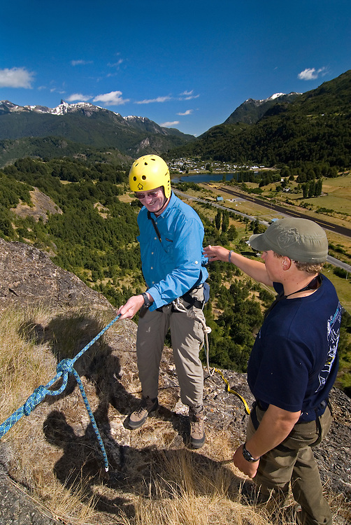Climbing instructor helping student before rappeling down a cliff above the town of Futaleufu, Chile.