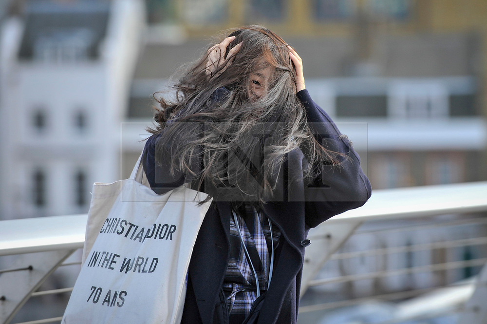 © Licensed to London News Pictures. 21/10/2017. London, UK. A tourist is buffeted by gusts crossing the Millennium Bridge as Storm Brian brings windy weather to the capital. Photo credit : Stephen Chung/LNP