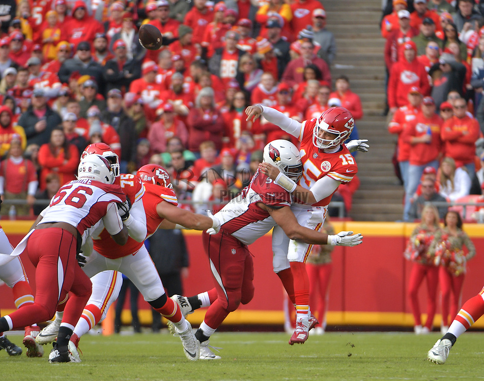 Nov 11, 2018; Kansas City, MO, USA; Kansas City Chiefs quarterback Patrick Mahomes (15) is hit by Arizona Cardinals defensive tackle Corey Peters (98) while throwing during the first half at Arrowhead Stadium. Mandatory Credit: Denny Medley-USA TODAY Sports
