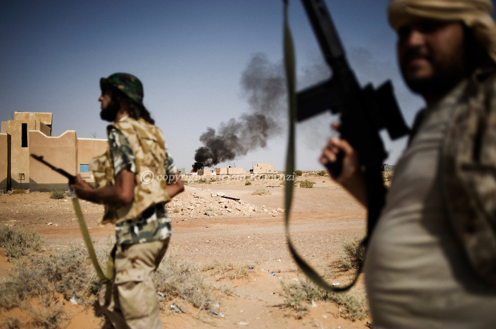 LIBYAN ARAB JAMAHIRIYA, Um al Far : Libyan rebel fighters walk through Um al Far after taking control of the village, on July 28, 2011. ALESSIO ROMENZI