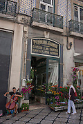 As a lady outside the Pequeno Jardim florists browses their display of flowers on the pavement, a cellist plays a sad lament tune for passers-by, on 13th July 2016, in Lisbon, Portugal. The florist is located at 61, Rua Garrett in the commercial heart of the Portuguese capital. (Photo by Richard Baker / In Pictures via Getty Images)