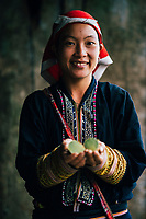 A young Red Dao woman holds out foraged roots in northern Vietnam.