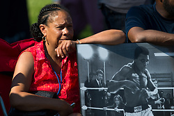 Anitra Luckett sits outside Muhammad Ali's boyhood home before passed by on Grand Avenue, Friday, June 10, 2016 at Muhammad Ali Funeral Procession in Louisville.