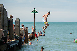 ©Licensed to London News Pictures. 25/07/2019. Aberystwyth, UK. People jumping off the jetty into the cool sea in Aberystwyth  on yet another scorching  day as a plume of hot air continues to dominate the UK, with the likelihood of record breaking temperatures of 38 or 39ºc in parts of the south east this afternoon. Photo credit : Keith Morris/LNP