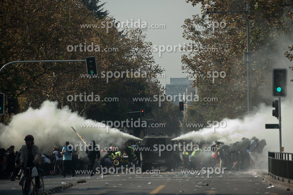 Riot police fire water cannon at protesting students in a march in Santiago, capital of Chile, on April 16, 2015. The march was held to demand the government fulfill its promise of free higer education, according to the organizers. EXPA Pictures &copy; 2015, PhotoCredit: EXPA/ Photoshot/ [e]JORGE VILLEGAS<br /> <br /> *****ATTENTION - for AUT, SLO, CRO, SRB, BIH, MAZ only*****
