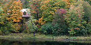 A log home along the Mississippi River is surrounded by trees beginning to turn color for fall - in Almonte, Ontario, Canada.