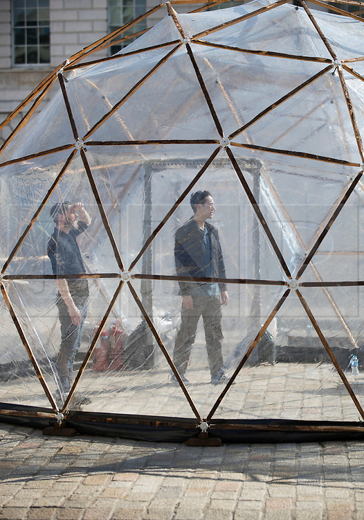 © Licensed to London News Pictures. 18/04/2018. London, UK. Visitors walk through one of British artist Michael Pinsky's Pollution Pods, a new sensory work, installed in the courtyard at Somerset House in London to mark Earth Day 2018. A series of five connecting domes recreate the pollution from London, Beijing, São Paulo, New Delhi and Tautra in Norway. Visitors are invited to experience first-hand the difference in the air quality of global environments. The Pollution Pods are open until 25th April 2018, including Earth Day on the 22nd April. Photo credit: Peter Macdiarmid/LNP