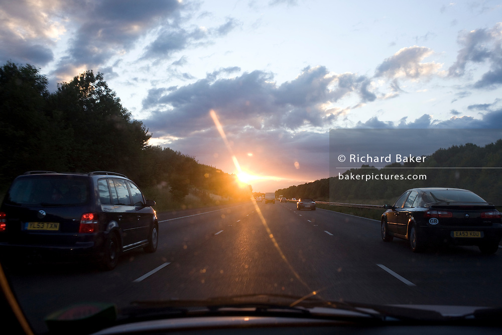 Driving into a setting sun while overtaking in the middle-lane with westbound traffic on Kent's M20 motorway