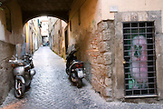 Viterbo, Italy old street with motorcycles and a picture of a pink poodle.